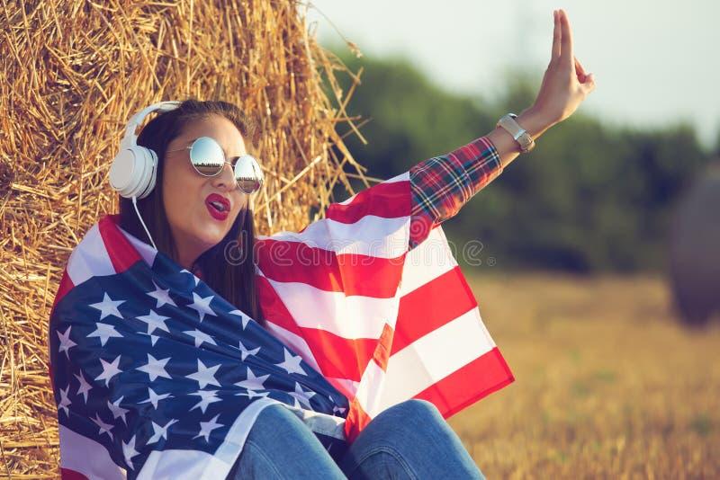 Muchacha hermosa que se sienta en el campo, con una bandera de los Estados Unidos de América en sus hombros fotografía de archivo