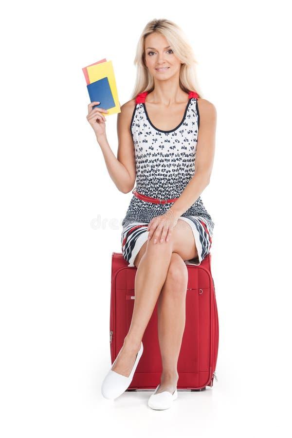 Muchacha hermosa que se sienta en el equipaje y la sonrisa fotos de archivo libres de regalías
