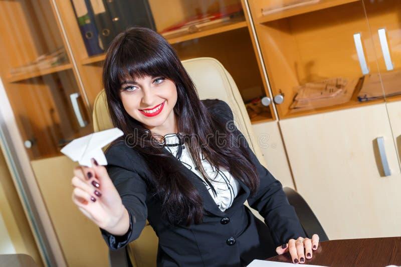 Muchacha hermosa que se sienta en el escritorio en la oficina fotos de archivo