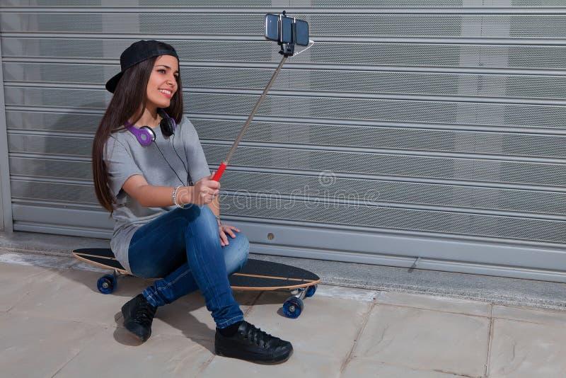 Muchacha hermosa que se sienta en el monopatín que toma el selfie imagenes de archivo