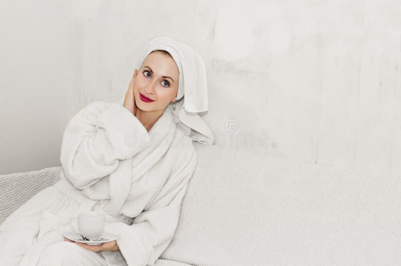 Muchacha hermosa que se sienta en el sofá en una albornoz mullida en un cuarto sin el papel pintado en las paredes Fondo blanco,  fotografía de archivo