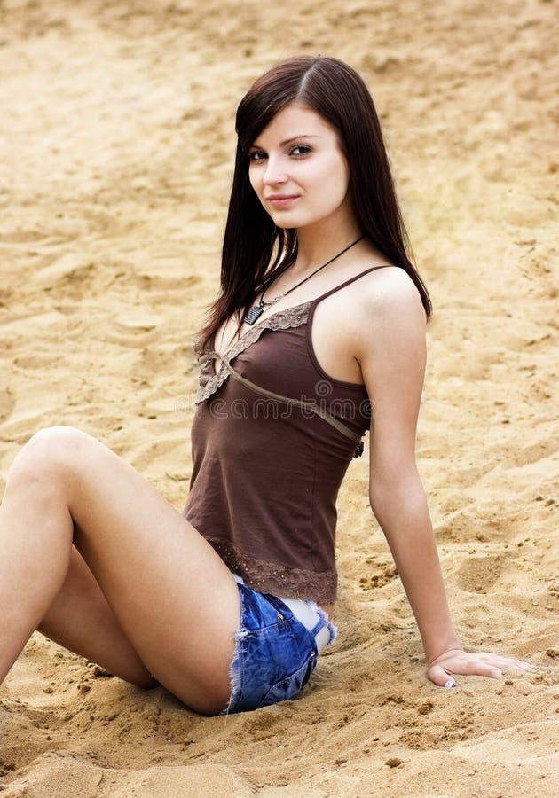 Muchacha hermosa que se sienta en la arena foto de archivo