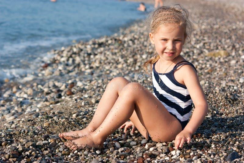 Muchacha hermosa que se sienta en la playa foto de archivo