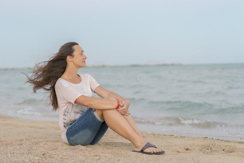 Muchacha hermosa que se sienta en la playa El centro envejeció a la mujer que descansaba en la playa cerca del mar mujer joven, h fotografía de archivo libre de regalías