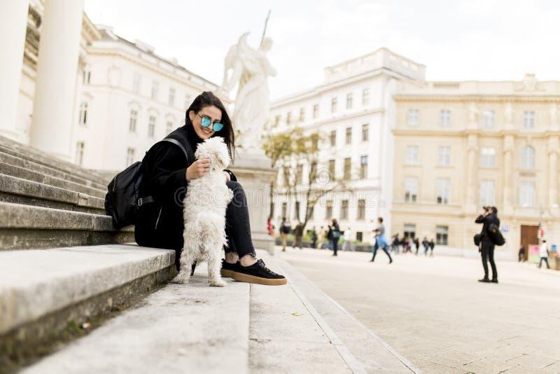 Muchacha hermosa que se sienta en las escaleras con su perro casero después de paseo adentro fotografía de archivo libre de regalías