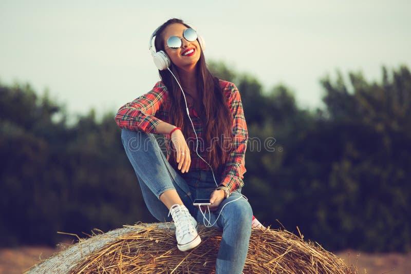 Muchacha hermosa que se sienta en un pajar, escuchando la música, disfrutando de puesta del sol fotografía de archivo libre de regalías