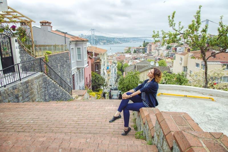 Muchacha hermosa que se sienta en una escalera en el distrito de Kuzguncuk imagen de archivo