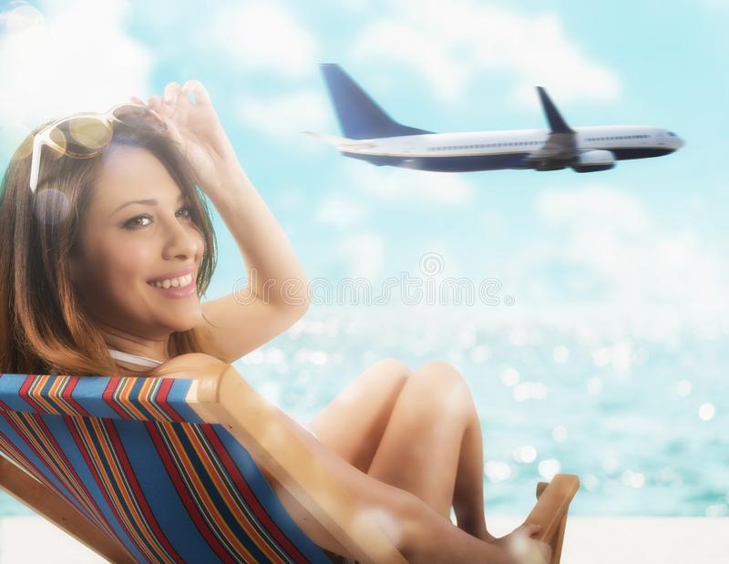 Muchacha hermosa que se sienta en una silla de cubierta en la playa en la puesta del sol con el aeroplano en fondo foto de archivo libre de regalías