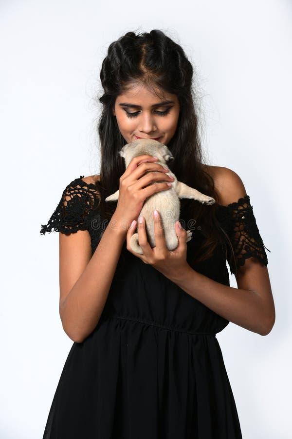 Muchacha hermosa que sostiene el perro del barro amasado del perrito disponible fotografía de archivo libre de regalías