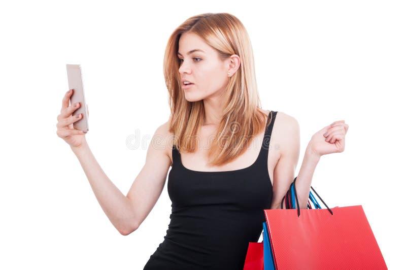 Muchacha hermosa que sostiene los panieres que hojean en smartphone imagenes de archivo