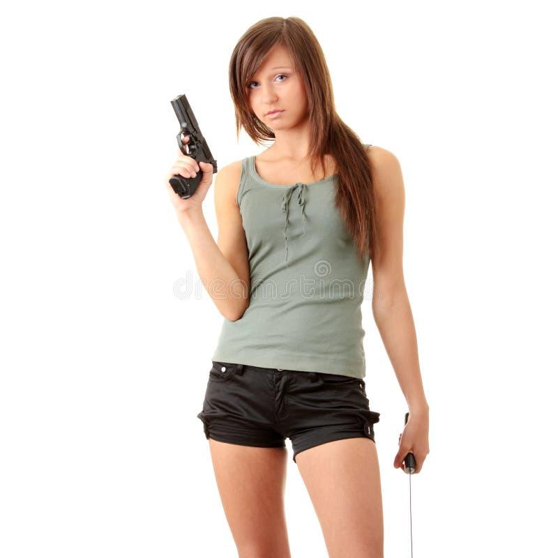 Muchacha hermosa que sostiene un arma negro imágenes de archivo libres de regalías