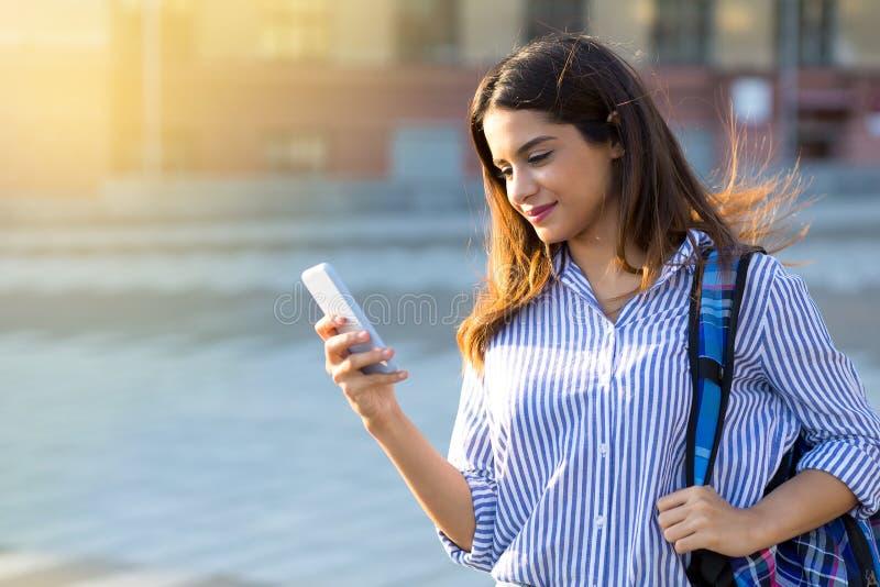 Muchacha hermosa que sostiene un teléfono, mandando un SMS a un mensaje que camina al aire libre y que disfruta de día soleado imagen de archivo libre de regalías