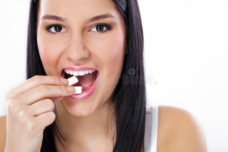 Muchacha hermosa que toma el chicle blanco, sonriendo fotos de archivo