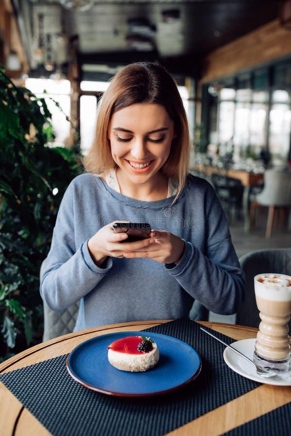 Muchacha hermosa que toma la imagen de la torta, sentándose en el café con la taza de latte foto de archivo