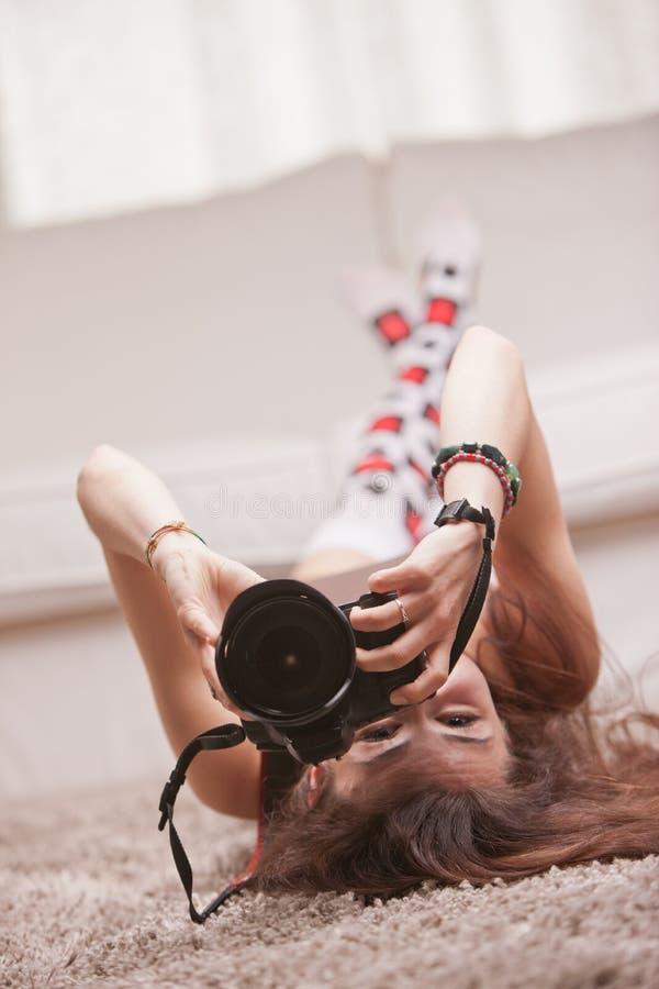 Muchacha hermosa que toma las fotografías en casa imagen de archivo libre de regalías