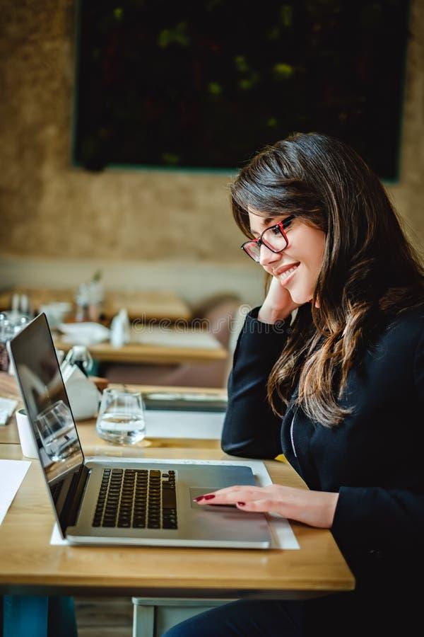 Muchacha hermosa que trabaja en el ordenador portátil en un café foto de archivo libre de regalías