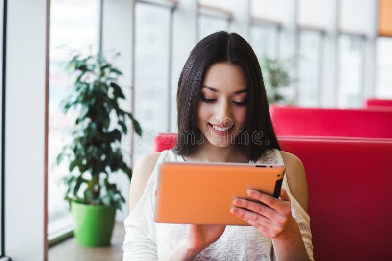 Muchacha hermosa que trabaja en una tableta y una sonrisa fotos de archivo
