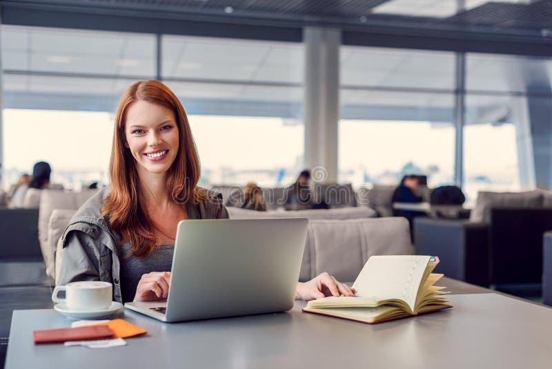 Muchacha hermosa que usa el ordenador portátil en aeropuerto imagenes de archivo