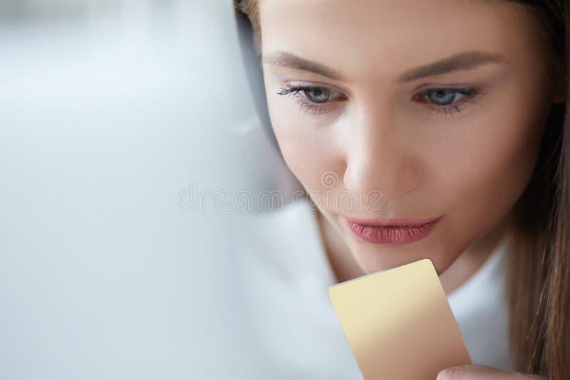 Muchacha hermosa que usa el ordenador portátil para hacer compras en línea con la tarjeta de crédito Mujer sonriente que usa el o imagenes de archivo