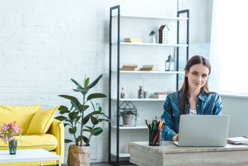 muchacha hermosa que usa el ordenador portátil y sonriendo en la cámara mientras que se sienta en el escritorio imagen de archivo libre de regalías