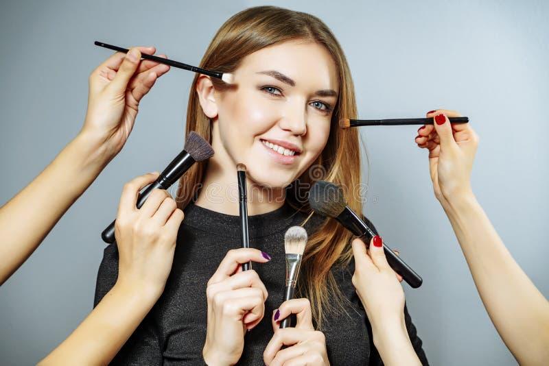 Muchacha hermosa rodeada por las manos de los artistas de maquillaje con los cepillos cerca de su cara Foto de la mujer feliz en  foto de archivo