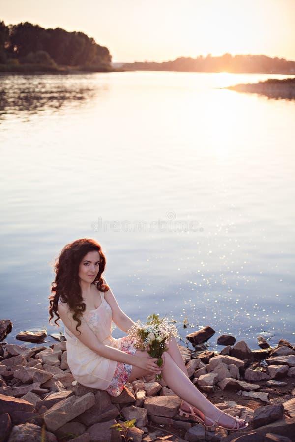 Muchacha hermosa romántica en la puesta del sol en el río imagenes de archivo