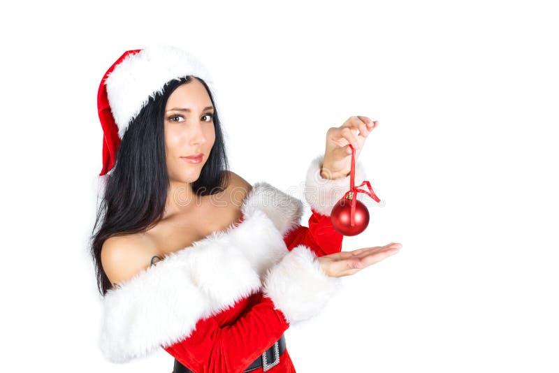Muchacha hermosa Santa Claus con el pelo oscuro en un traje en un fondo blanco que sostiene un juguete de la Navidad aislante imágenes de archivo libres de regalías