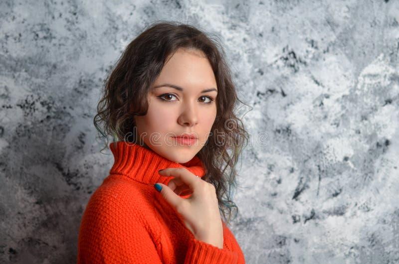 Muchacha hermosa sensual que presenta en suéter rojo fotografía de archivo libre de regalías