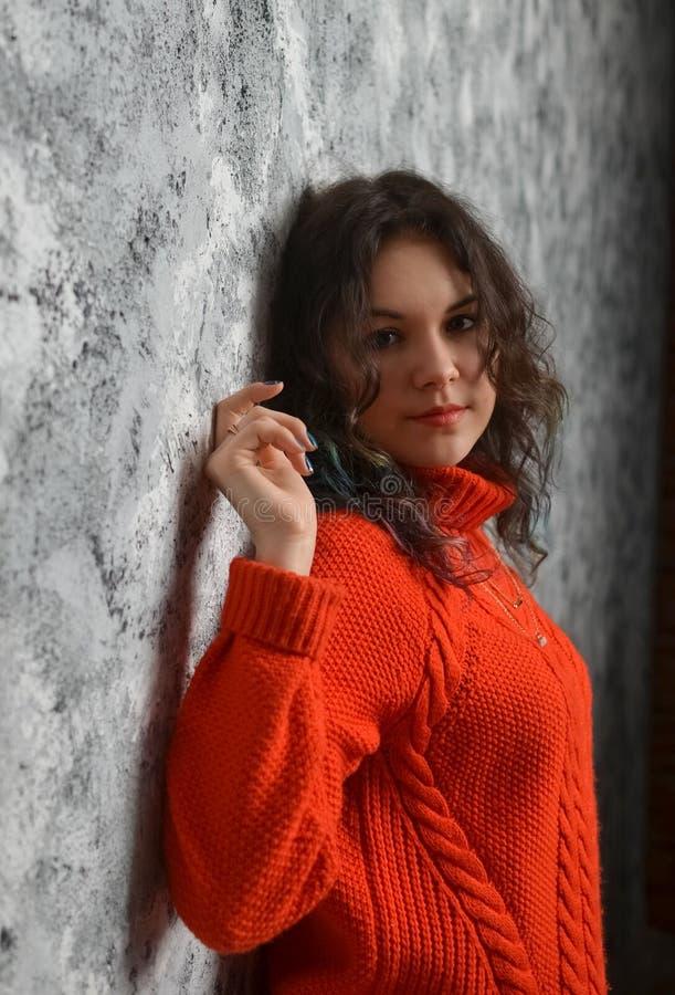 Muchacha hermosa sensual que presenta en suéter rojo fotos de archivo