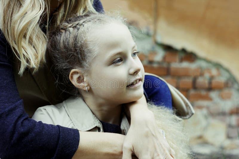 Muchacha hermosa sonriente 7 años con los ojos azules, abrazando a su mamá fotografía de archivo libre de regalías