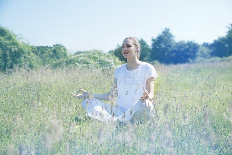 Muchacha hermosa sonriente de la yoga que medita para la franqueza en el ambiente verde imagenes de archivo