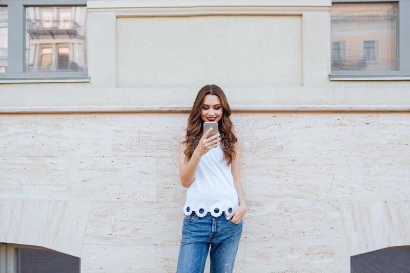 Muchacha hermosa sonriente de los jóvenes que usa su teléfono al aire libre foto de archivo