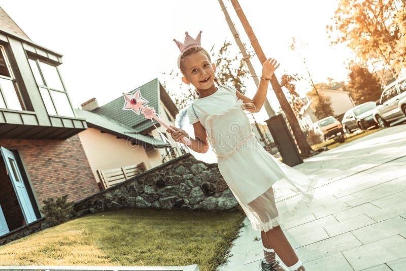 Muchacha hermosa sonriente en el vestido blanco y la corona rosada que son un carácter fantástico imagenes de archivo
