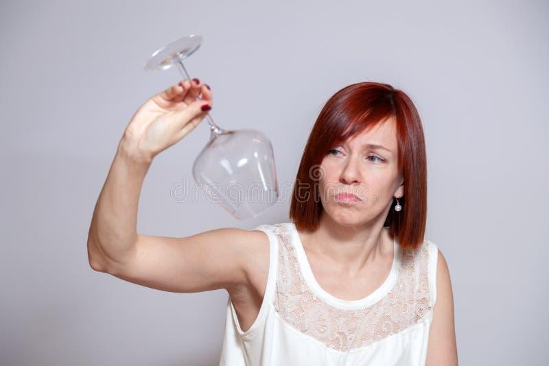 Muchacha hermosa triste joven que sostiene una copa de vino invertida cristalina transparente vacía Concepto del Sommelier, vino  imágenes de archivo libres de regalías