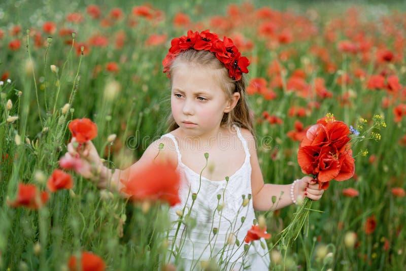 Muchacha hermosa ucraniana en el campo de amapolas y del trigo retrato al aire libre en amapolas fotos de archivo libres de regalías