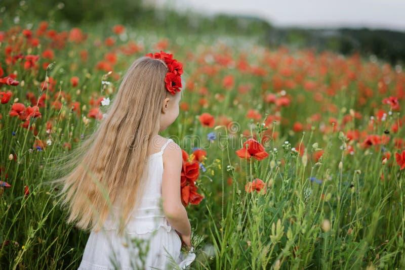 Muchacha hermosa ucraniana en el campo de amapolas y del trigo retrato al aire libre en amapolas fotografía de archivo