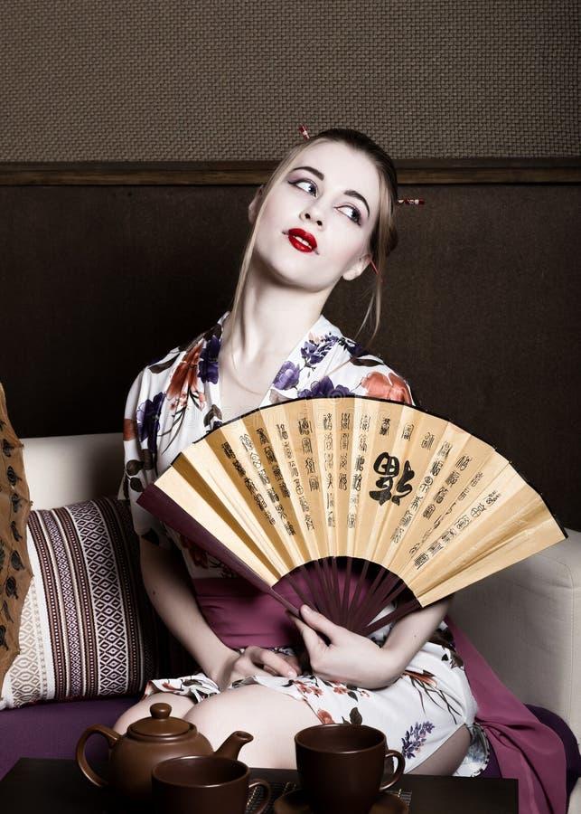 Muchacha hermosa vestida como geisha, ella sostiene una fan china El maquillaje y el pelo del geisha se vistieron en un kimono r imagen de archivo libre de regalías