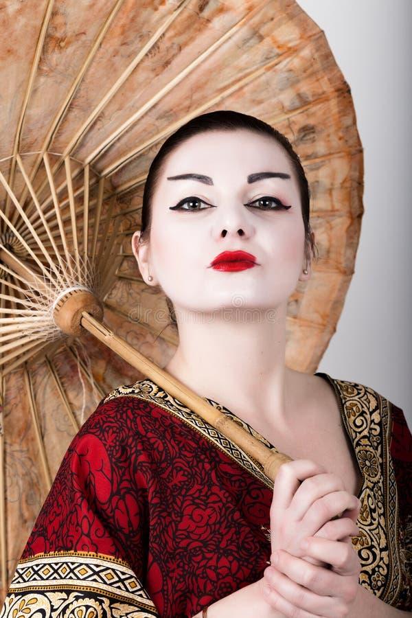 Muchacha hermosa vestida como muchacha de geisha que sostiene un paraguas chino El maquillaje y el pelo del geisha se vistieron e fotos de archivo