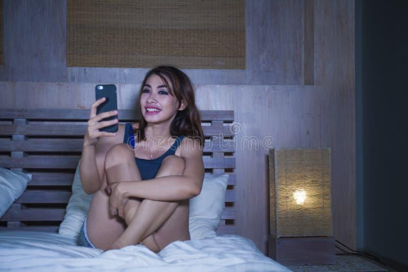 Muchacha hermosa y feliz joven que se sienta en la cama que sonríe y que liga en los medios sociales app de Internet usando el te imágenes de archivo libres de regalías