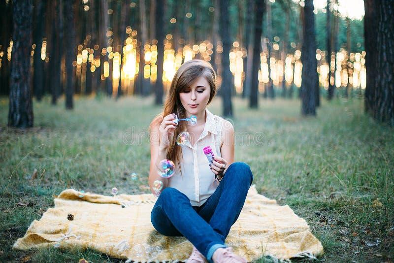 Muchacha hermosa y sonriente joven que hace burbujas de jabón imagen de archivo libre de regalías