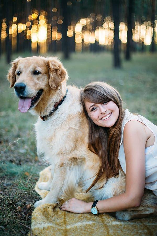 Muchacha hermosa y sonriente joven que juega con un perro imagen de archivo libre de regalías