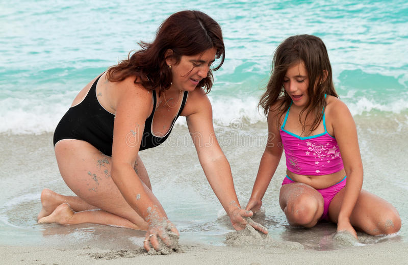 Muchacha hermosa y su madre que juegan en la arena foto de archivo
