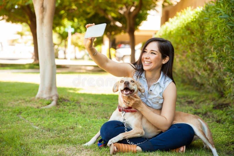 Muchacha hermosa y su perro que toman un selfie fotos de archivo libres de regalías