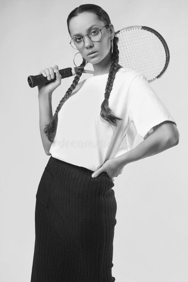 Muchacha hispánica encantadora hermosa en la camiseta blanca con ra del tenis imagen de archivo