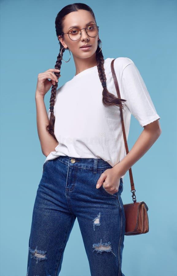 Muchacha hispánica encantadora hermosa en la camiseta blanca, vaqueros y vidrios imágenes de archivo libres de regalías