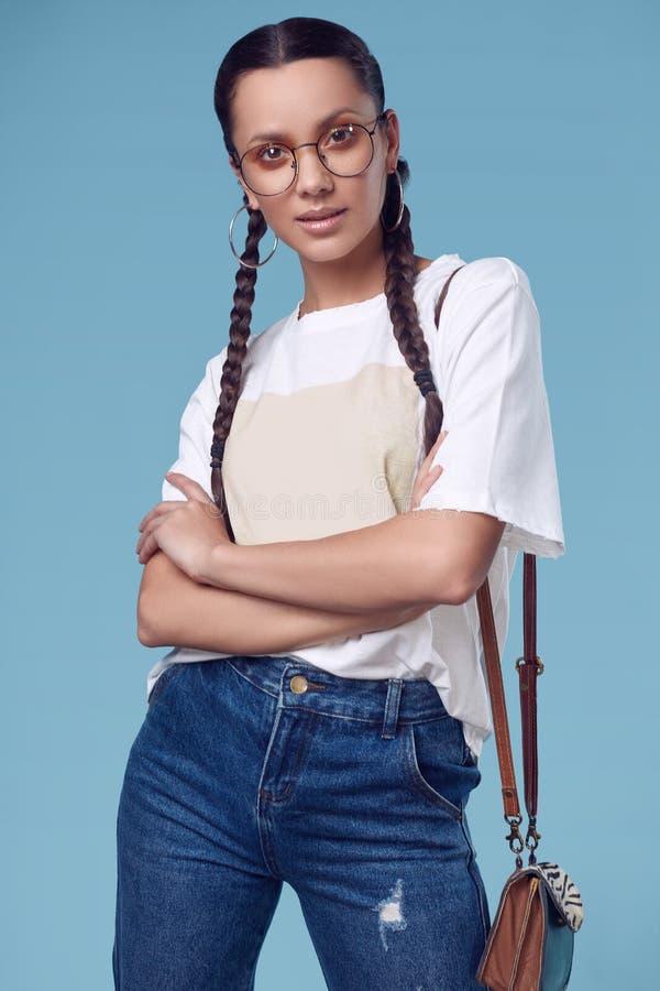 Muchacha hispánica encantadora hermosa en la camiseta blanca, vaqueros y vidrios fotografía de archivo