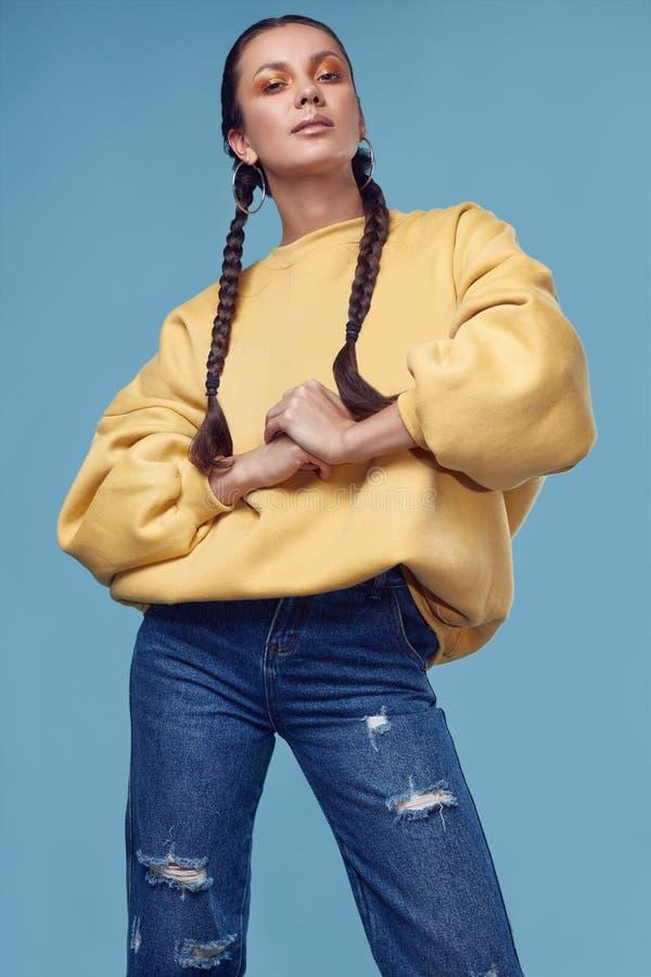 Muchacha hispánica encantadora hermosa en vaqueros y sudadera con capucha amarilla imagenes de archivo