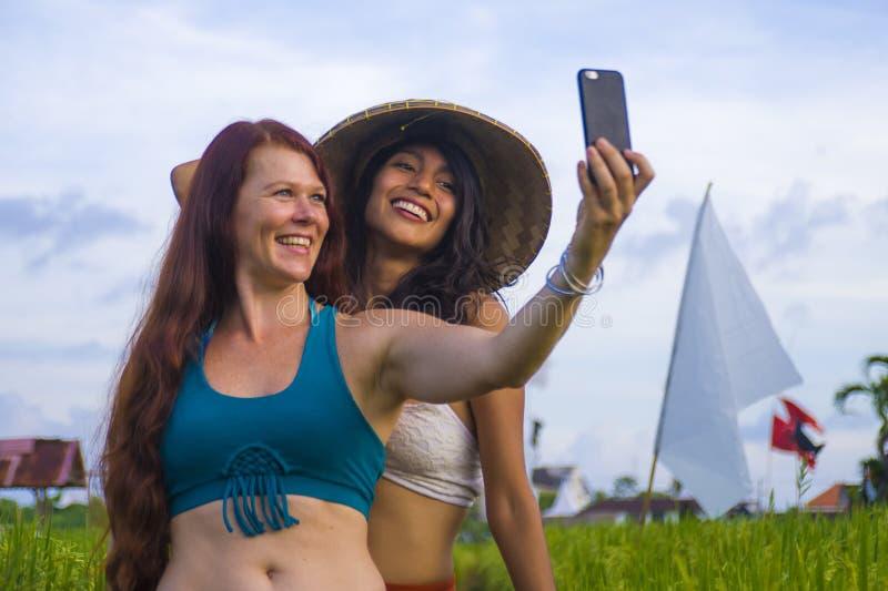 Muchacha hispánica feliz y hermosa joven en sombrero asiático tradicional del granjero y la mujer caucásica que toman a novias el foto de archivo