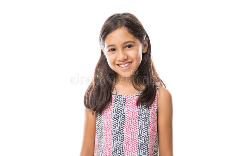 Muchacha hispánica joven sonriente que plantea y que mira el ove de la cámara foto de archivo