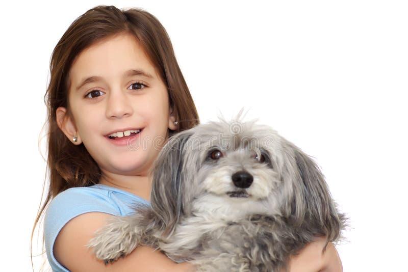 Muchacha hispánica que abraza su perro aislado en w fotos de archivo